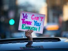 A person holds a sign
